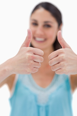 Portrait of a woman with the thumbs up against a white background Stock Photo - 11686050