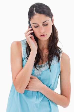 Portrait of a sad woman making a phone call against a white background photo