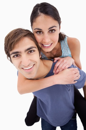 Portrait of a young man holding his girlfriend on his back against a white background photo