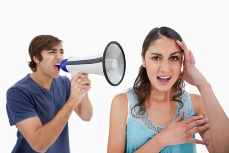 Man shouting at her girlfriend through a megaphone against a white background photo