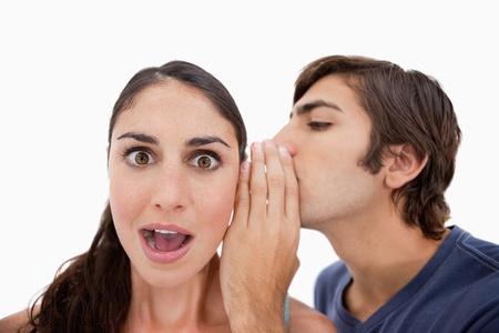 Man whispering something shocking to his fiance against a white background photo