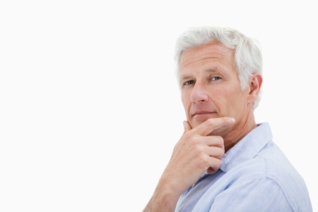 Mature man thinking against a white background Stock Photo - 11687265