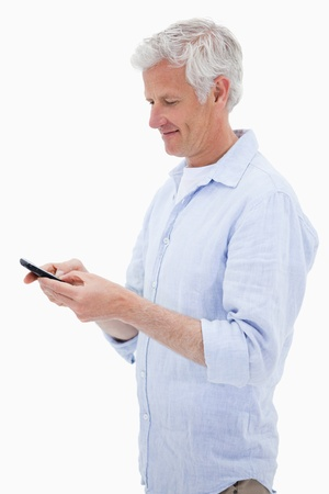 Portrait of a man using his mobile phone against a white background photo