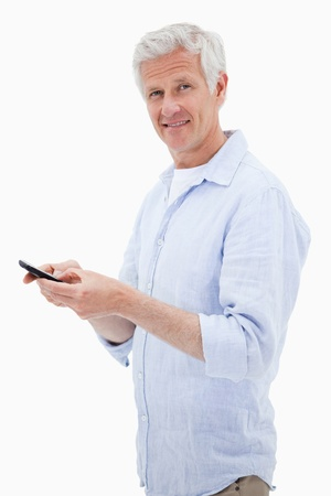 Portrait of a man using his mobile phone while looking at the camera against a white background photo