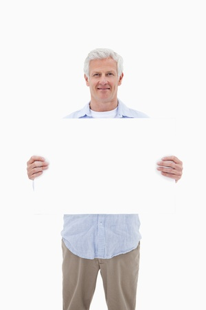 Portrait of a mature man holding a blank panel against a white background photo