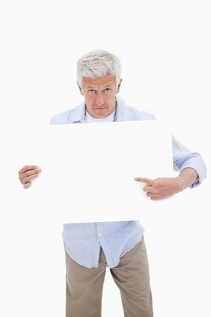 Portrait of a mature man pointing at a blank board against a white background photo