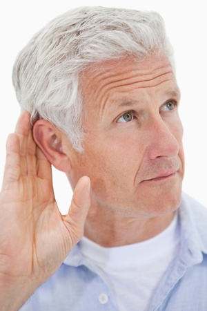 Portrait of a mature man giving his ear against a white background photo