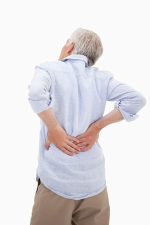 chronic back pain: Portrait of a man having a back pain against a white background