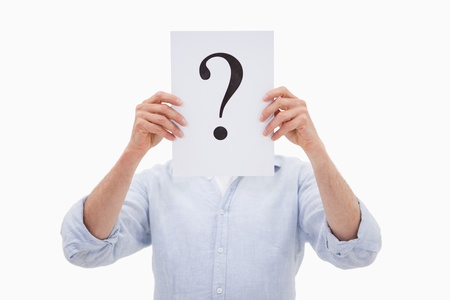 interrogation mark: Portrait of a man hiding his face behind a question mark against a white background