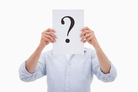 punto di domanda: Ritratto di un uomo che nasconde il viso dietro un punto interrogativo su uno sfondo bianco Archivio Fotografico