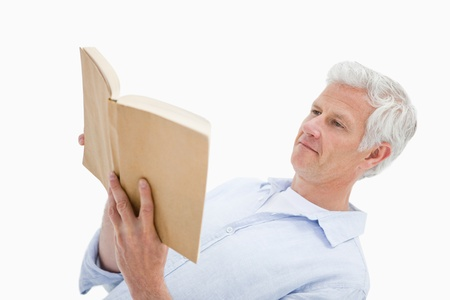 Mature man reading a book against a white background photo