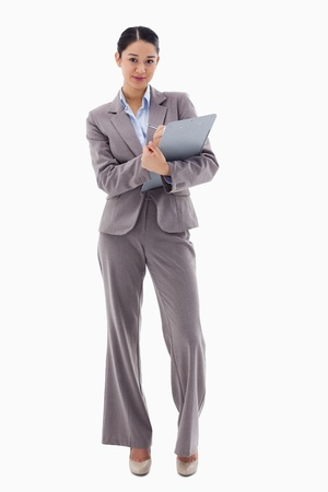 Portrait of a brunette businesswoman taking notes against a white background photo