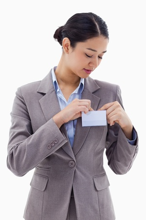 Portrait of a businesswoman clipping her badge against a white background photo
