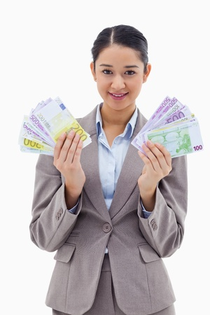 Portrait of a happy businesswoman holding bank notes against a white background