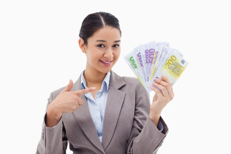 Smiling businesswoman holding bank notes against a white background Stock Photo - 11686742