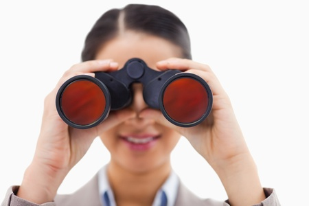Close up of a businesswoman looking through binoculars against a white background photo