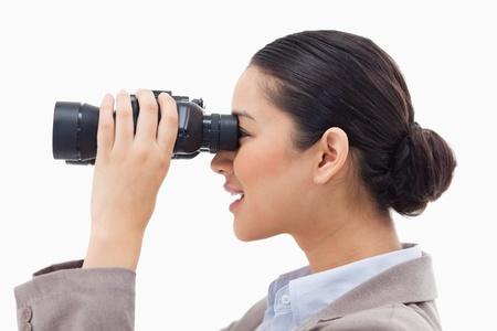 Vista lateral de una mujer de negocios mirando a través de unos prismáticos sobre un fondo blanco