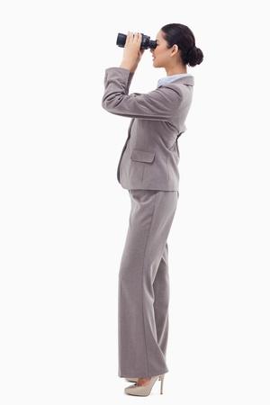 t�lescopes: Portrait d'une femme d'affaires heureux regardant avec des jumelles sur un fond blanc Banque d'images