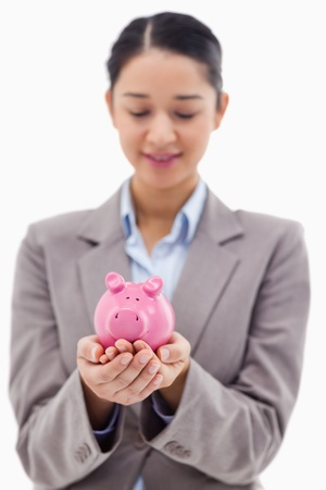 Portrait of a young businesswoman holding a piggy bank against a white background photo