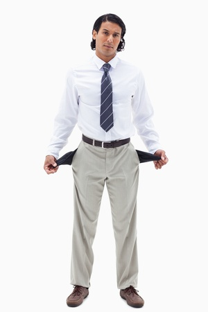 moneyless: Portrait of a broke businessman showing his empty pockets against a white background