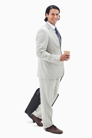 Side view of businessman with coffee and wheely bag against a white background photo