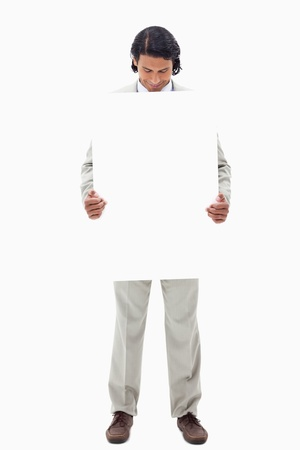 Businessman looking at blank sign he is holding against a white background Stock Photo - 11687600