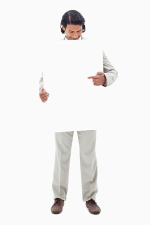 Businessman looking and pointing at blank sign in his hands against a white background Stock Photo - 11687596