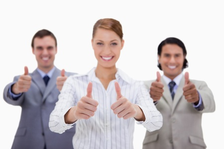 Businessteam giving thumbs up against a white background photo