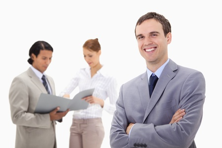 Smiling young businessman with talking colleagues behind him against a white background Stock Photo - 11686672