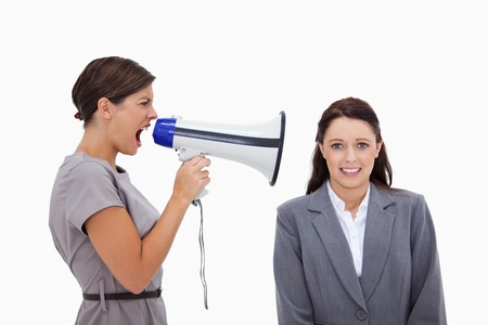 Businesswoman using megaphone to yell at colleague against a white background Stock Photo - 11686706