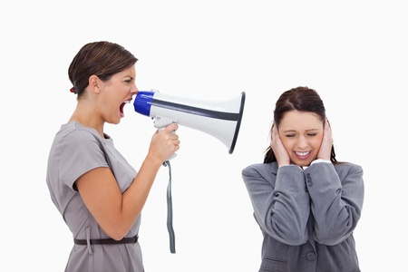 woman screaming: Businesswoman yelling at colleague with megaphone against a white background Stock Photo