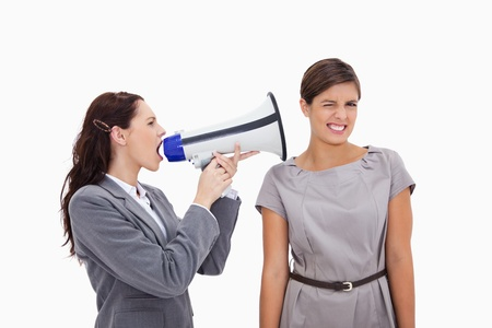 Businesswoman with megaphone yelling at colleague against a white background photo