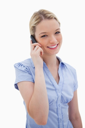 Smiling woman using cellphone against a white background Stock Photo - 11686656