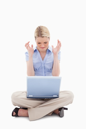 Woman sitting and angry about her laptop against a white background photo