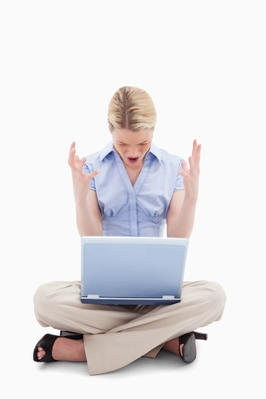 Sitting woman yelling at her laptop against a white background photo
