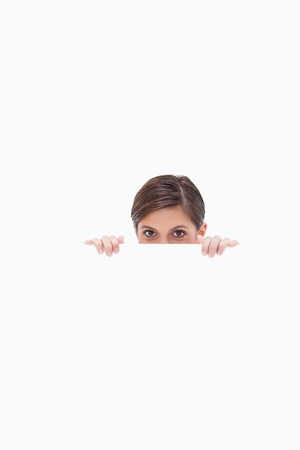 sneaky: Sneaky woman looking over blank wall against a white background Stock Photo