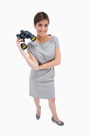 Woman standing with binoculars against a white background photo