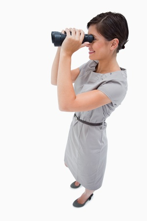 Side view of woman using spyglasses against a white background photo