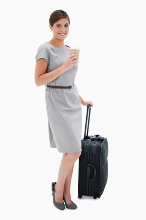Smiling woman with coffee and wheely bag against a white background photo