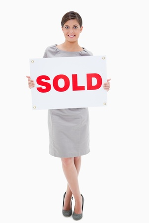 Woman holding sold sign against a white background photo