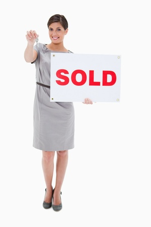 Woman with sold sign handing over key against a white background photo