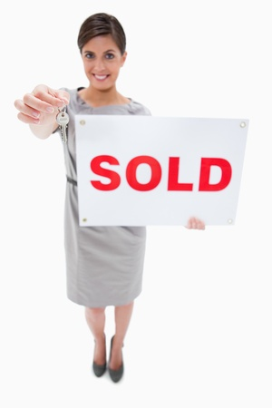 Real estate agent with sold sign handing over key against a white background photo