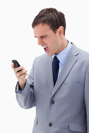 Businessman yelling at his cellphone against a white background photo