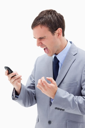 Angry businessman yelling at his cellphone against a white background photo