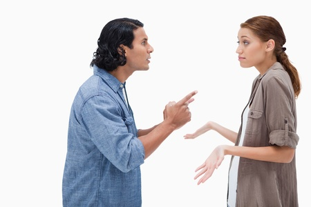 Side view of man asking his clueless girlfriend against a white background photo