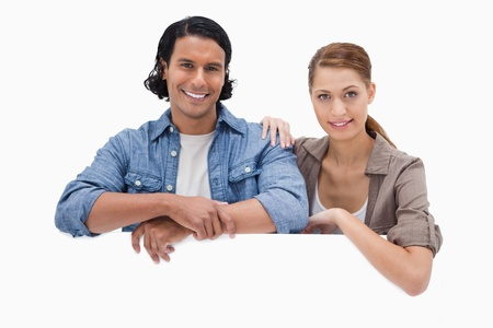 Couple leaning on blank wall against a white background photo