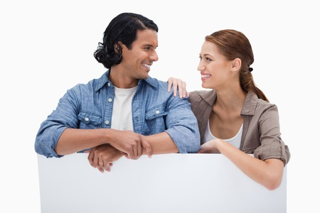 Smiling couple leaning on blank wall against a white background photo