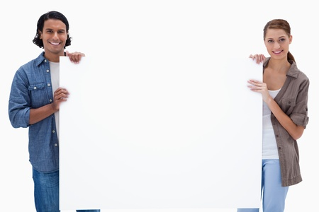 Couple holding a blank sign against a white background photo