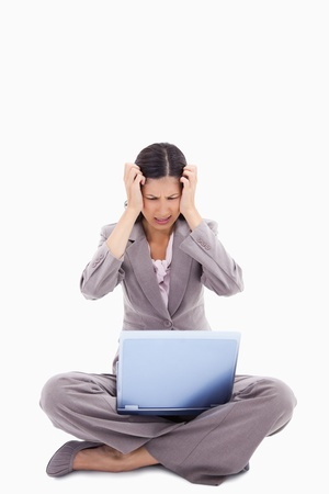 Sitting woman having trouble with notebook against a white background photo