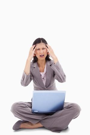 computer problems: Laptop donna seduta d� il mal di testa contro uno sfondo bianco